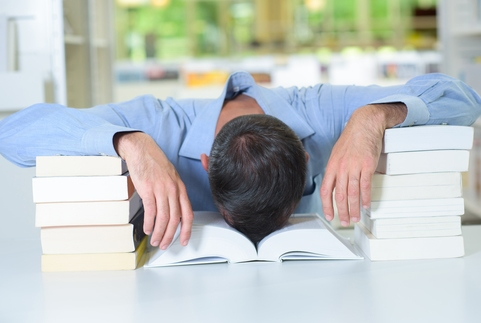 Man with head slumped in a book